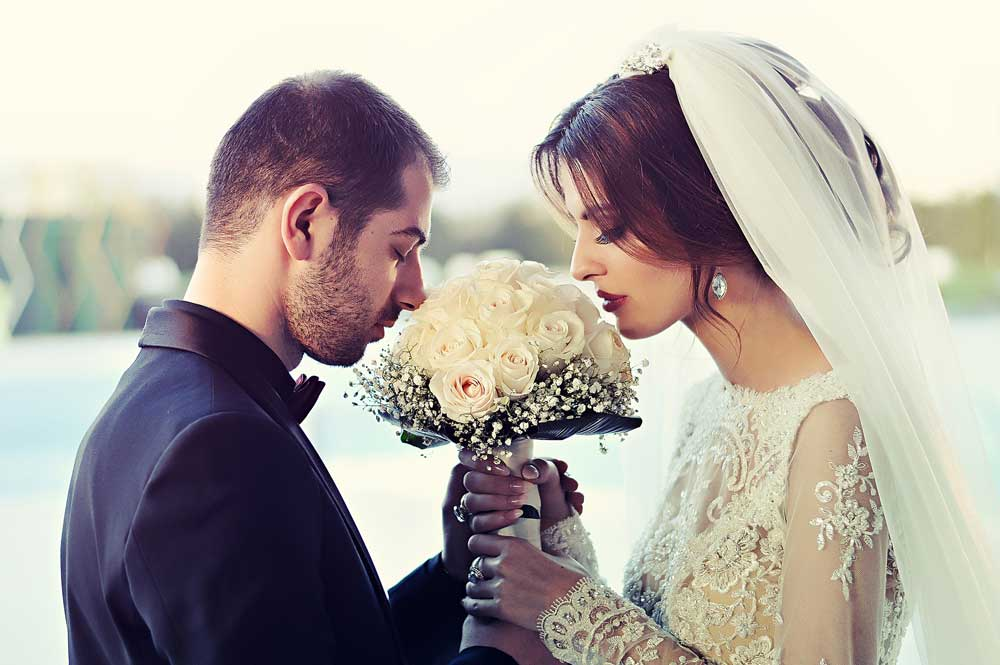 Bride and Groom Smelling Flowers